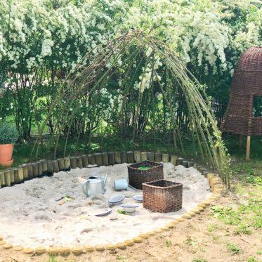 Bodennahe Natur Sandkiste aus Palisaden bauen mit einem Weidendach,hier erfahrt ihr wie ihr sie ganz einfach selberbauen könnt, inkl. Tipps zum erstellen eines Weidendaches als Sonnenschutz. Noch mehr Garten Tipps, und DIY rund um Garten und Kinder findet ihr aus www.elfenkindberlin.de